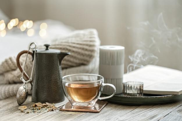 Nature morte confortable avec une tasse de thé en verre, une théière et des bougies sur un arrière-plan flou avec bokeh.