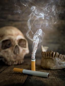 Nature morte crâne et cigarette brûlée avec de la fumée sur du bois.