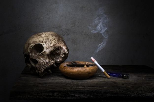 Nature morte crâne et cigarettes les gens fument la cigarette et obtiennent le corps de la toxine