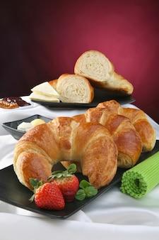 Nature morte avec croissant, petit-déjeuner avec pâtisserie, fruits et confiture.