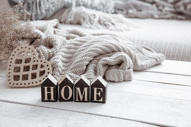 Nature morte dans le style hygge avec maison de mot en bois, coeur et élément tricoté. concept de confort de la maison et de style moderne.