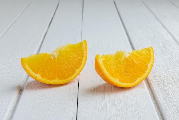 Nature morte demi-croissant de fruits orange frais sur une table en bois blanc vintage