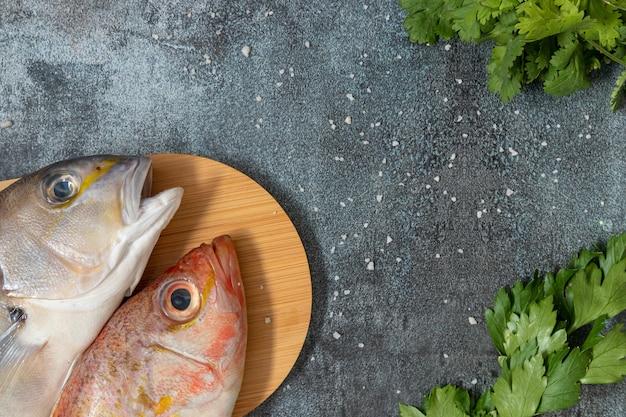 Nature morte avec deux poissons frais et ingrédients péruviens pour cuisiner