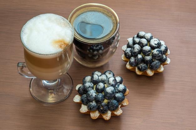 Nature morte avec deux tasses de café (expresso et latte) et le gâteau aux myrtilles