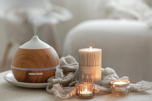 Nature morte avec diffuseur d'arômes pour humidifier l'air et bougies allumées.