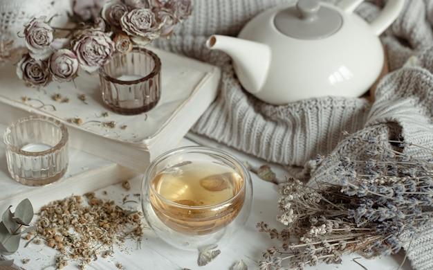 Nature morte douce et lumineuse avec des bougies, une tasse de thé, une théière et des herbes sèches.