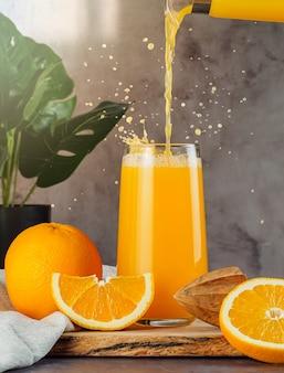 Nature morte avec du jus d'orange frais dans un verre avec des éclaboussures et des gouttes. le jus s'écoule de la carafe dans le verre. en arrière-plan, il y a un monstera, un reflet ensoleillé. ensemble de 3 jus.