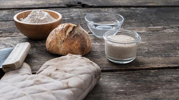 Nature morte avec du pain au levain maison fraîchement cuit à côté de la mitaine de cuisine, de la levure de démarrage, de la farine et de l'eau.