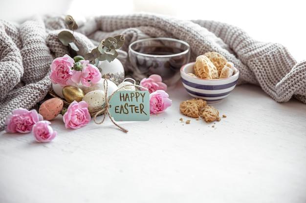 Nature morte avec du thé, des biscuits, des œufs, des fleurs et l'inscription joyeuses pâques sur la carte postale