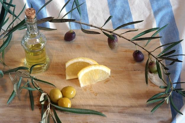 Nature morte à l'espagnol un jambon pata negra, olives et huile d'olive dans une bouteille sur une planche à découper en bois.