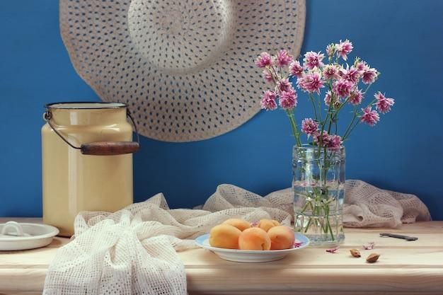 Nature morte estivale avec un bouquet, des fruits et un chapeau en osier. fleurs dans un vase et abricots.
