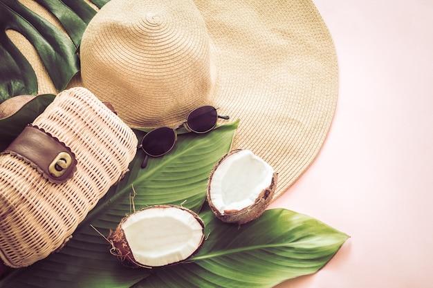 Nature morte d'été élégante avec chapeau de plage et noix de coco sur fond rose, pop art. vue de dessus, gros plan, concept créatif