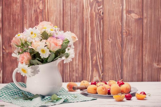 Nature morte d'été avec des pêches, des cerises et des fleurs sur une table en bois