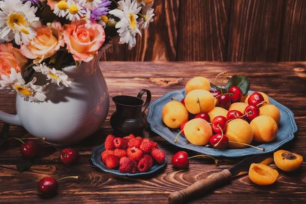 Nature morte d'été avec pêches, framboises, cerises et fleurs sur une table en bois