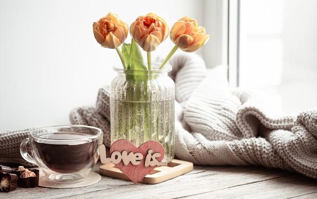 Une nature morte festive avec l'inscription love it, des fleurs dans un vase et une tasse de thé et des détails de décoration.