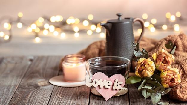 Une nature morte festive avec un verre dans une tasse, des fleurs et des détails de décoration