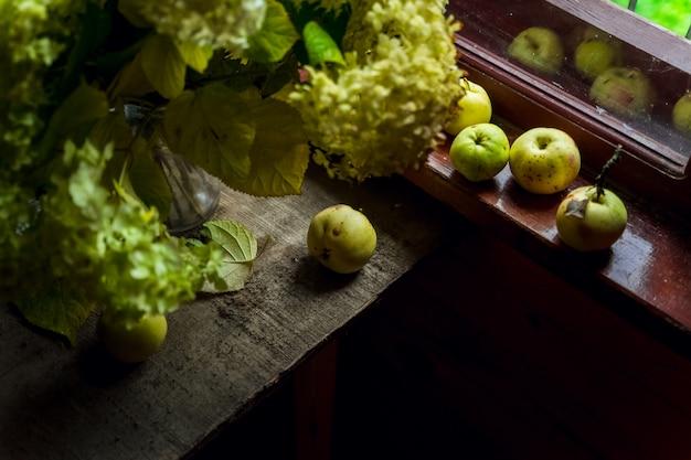 Nature morte avec des fleurs d'hortensia vert et un bouquet de pommes vertes par la fenêtre d'une maison de campagne en bois