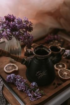 Nature morte de fleurs lilas, café sur un plateau en bois