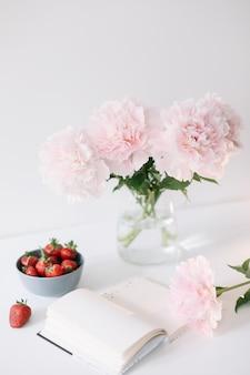Nature morte avec des fleurs de pivoine rose dans un vase, des fraises fraîches et un livre sur une table