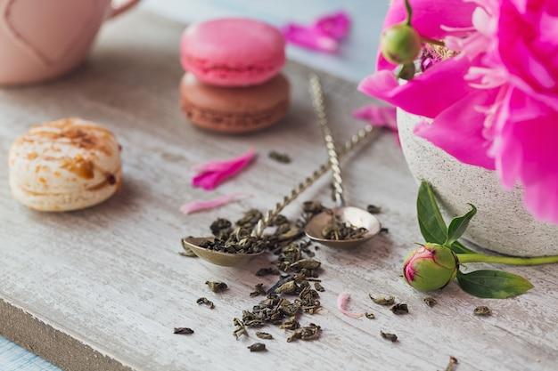 Nature morte avec des fleurs de pivoine rose et une tasse de thé à base de plantes ou vert sur fond de bois rustique
