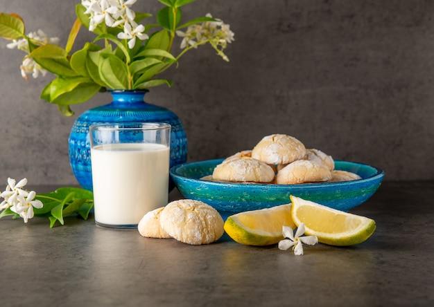 Nature morte sur fond sombre. biscuits au citron et une tranche de citron sur la table, un verre de lait et des fleurs dans un vase