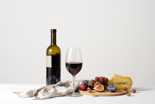 Nature morte avec fond de vin rouge, fromage et fruits