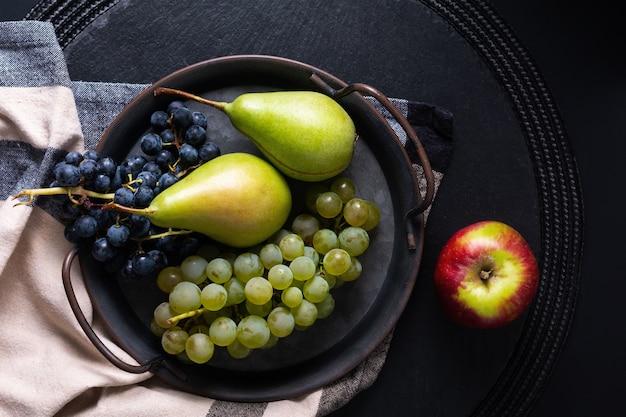 Nature morte fruit concept poire et raisin dans un plateau en fer vintage avec copie espace
