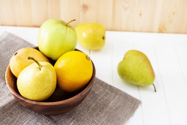 Nature morte fruit, pomme, poire, mangue, assiette en bois citron.