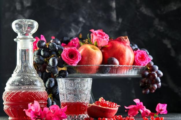 Nature morte de fruits d'automne frais et de jus de grenade dans une carafe et un verre.