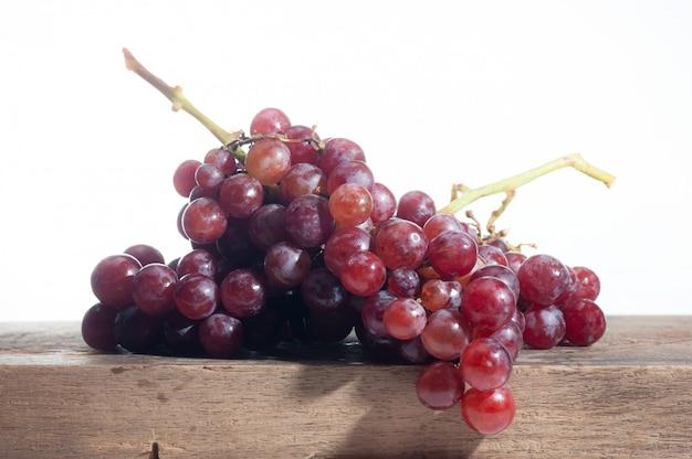Nature morte de fruits de raisin mis sur vieux bois, fond blanc
