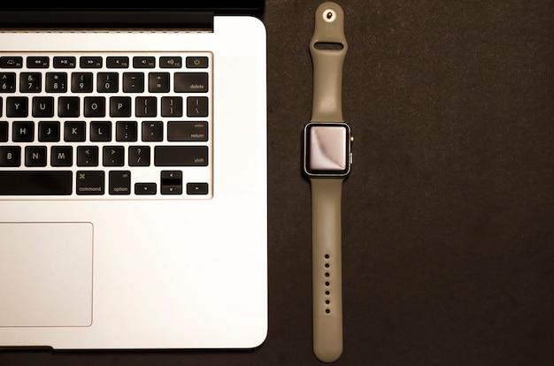 Nature morte de gadgets: ordinateur portable gris, smartwatch sur fond noir. composition des appareils