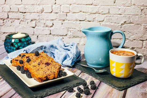 Nature morte de gâteau aux fruits sauvages avec une tasse de lait avec du cacao et un pot à lait.