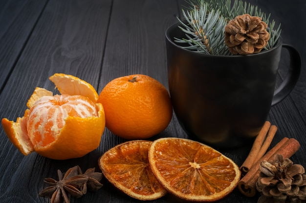 Nature morte d'hiver de noël: mandarines, oranges séchées, bâtons de cannelle et étoiles d'anis sur une surface noire texturée