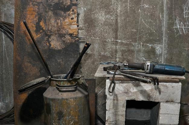 Nature morte industrielle - outils sur le piédestal et pièces métalliques durcies dans une boîte sur fond de mur de béton gris