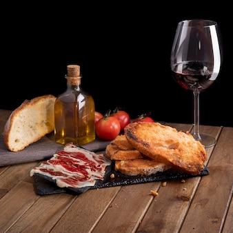 Nature morte de jambon ibérique avec du pain de tomate sur un plateau en pierre d'ardoise et un verre de vin. fond noir.