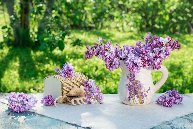 Nature morte avec lilas, cercueil, coquille posée sur une serviette de table sur fond de verdure