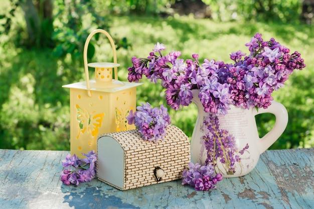 Nature morte avec un lilas dans un pichet, un cercueil, une lampe de poche sur une table en bois sur un fond de verdure