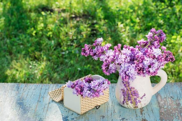 Nature morte avec un lilas dans un pichet, un cercueil sur une table en bois sur un fond de verdure