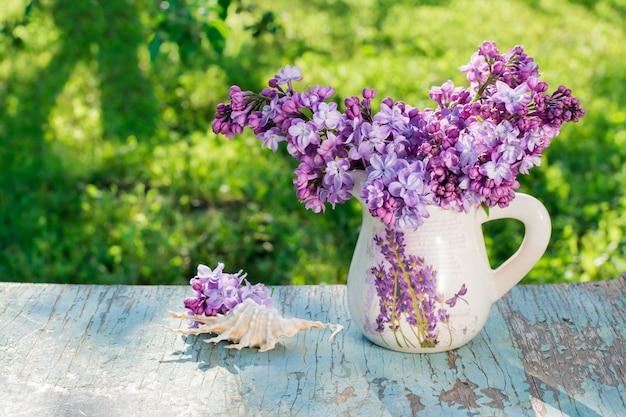 Nature morte avec un lilas dans un pichet, une coquille sur une table en bois sur un fond de verdure