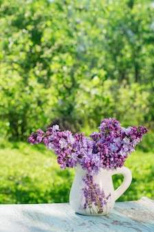 Nature morte avec des lilas dans un pichet sur une table en bois sur fond de verdure