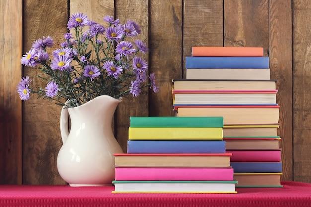 Nature morte avec des livres et un bouquet d'automne contre des planches.