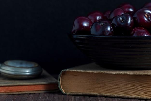 Nature morte avec des livres cerises et horloge
