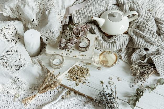 Nature morte lumineuse et confortable avec des bougies, du thé, une théière et des fleurs comme décor.