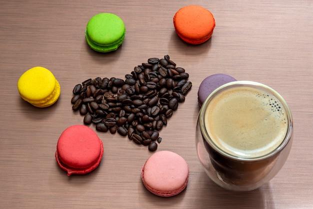 Nature morte avec macarons, tasse à expresso et coeur de grains de café