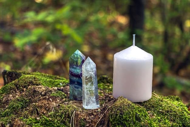 Nature morte magique avec fluorite, cristal de quartz et bougie rose.