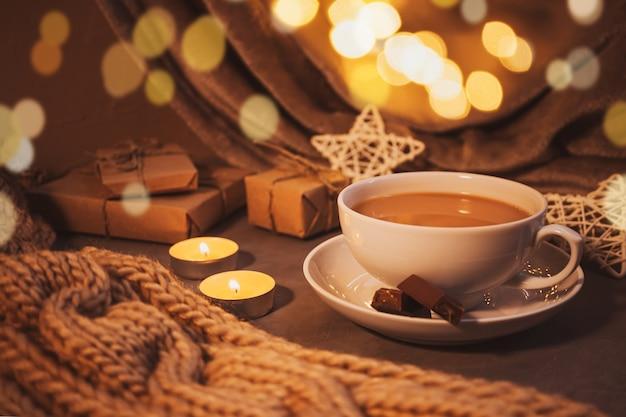 Nature morte à la maison confortable : tasse blanche avec café, écharpe en gros tricot, guirlande, bougies et cadeaux. le concept de l'hiver à venir, du réveillon de noël et du nouvel an. nuances chaudes, gros plan.