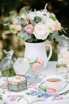 Nature morte mariées matin, plat avec une tasse de thé, verre à champagne, alliances et bouquet de fleurs