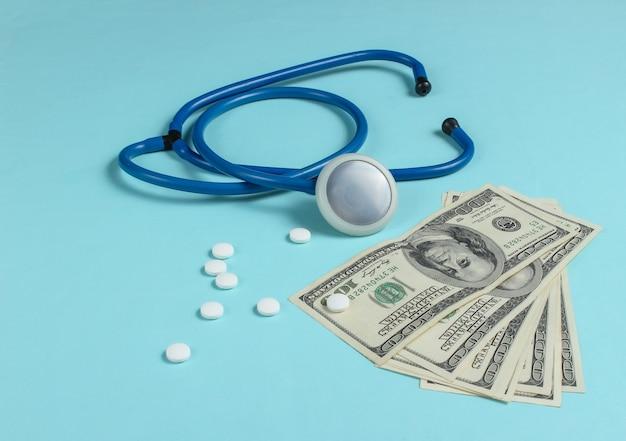Nature morte médicale. médecine payée. stéthoscope avec pilules, billets de cent dollars sur fond bleu.