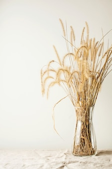 Nature morte à la mode moderne d'un bouquet de fleurs séchées dans un vase en verre sur une table en bois. espace pour le texte ou les annonces