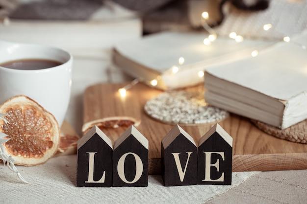 Nature morte avec le mot amour en bois, une tasse de boisson et des détails de décoration cosy sur un arrière-plan flou avec des lumières.